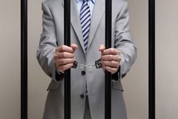 Businessman behind bars in prison concept for white collar crime