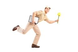 Full length portrait of a mailman delivering flowers, isolated on white background