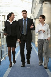 Business portrait of tree presons - young man and two women having nice chat talk on modern office corridor