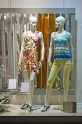 store window with dressed mannequins in shopping mall