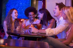 Group of young adults in a nightclub talking and laughing