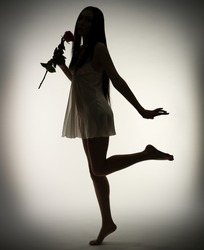 Silhouette of young girl with rose flower on gray background