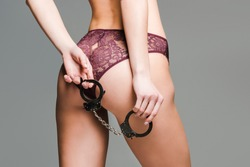 lady in pink lacy underwear holds handcuffs