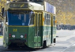 A classic green and gold Melbourne tram.