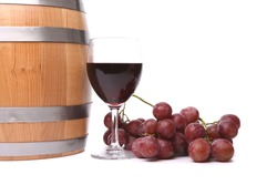 A glass of red wine with grapes and barrel on the white background.