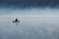 A fisherman starts working in a misty morning..