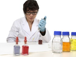 A scientist uses a pipette and spotting plate in laboratory research.