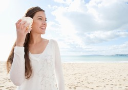 Young attractive healthy woman on a white sand beach holding a sea shell against her ear and listening to the sound of waves smiling, during a vacation trip away.