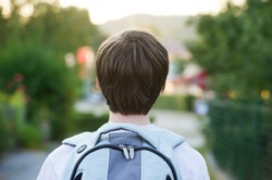 Teen wearing a school bag heading to school.
