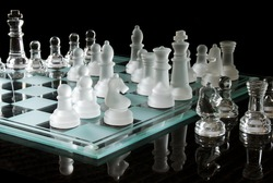Chess game made of glass with reflection.