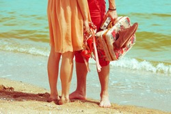 Young married couple standing together on beach holding their photo camera and shoes. Sunny summer day. Copy-space. Outdoor shot