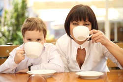 young mom having tea with her son in street cafe