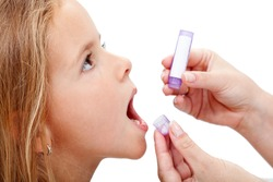 Young girl taking granules of homeopathic medication - closeup