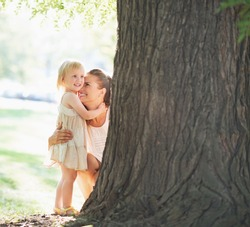 Happy mother and baby near tree