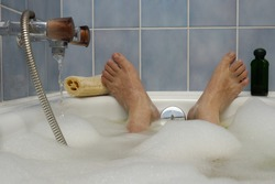 A man's feet, poking out of a bubble bath, with water running in to the side. A loofah and bottle of bath lotion to either side. Space for text on the blue tiled wall above the feet.