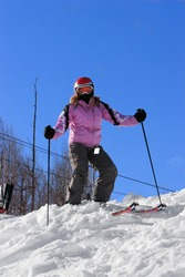 Woman standing at the top of a ski hill.