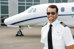 Confident pilot smiling in front of private jet