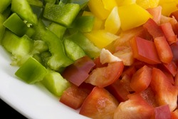 diced green, red and yellow bell pepper on a white plate ready for cooking or salad