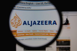LISBON - JANUARY 25, 2014: Photo of Aljazeera homepage on a monitor screen through a magnifying glass.