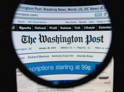 LISBON, PORTUGAL - FEBRUARY 8, 2014: Photo of The Washington Post homepage on a monitor screen through a magnifying glass.