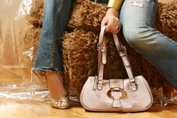 A fashion shoot of the legs of a female model in jeans.  Model is holding a pink leather bag in her hand.
