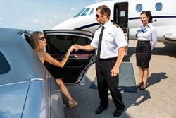 Full length of pilot helping elegant woman stepping out of car at airport terminal