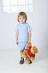 Young sad girl standing and holding teddy bear in hand. She's looking at camera. Front view.