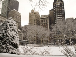 This is a snowy view of some buildings from Bryant Park in Manhattan.