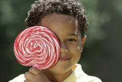 Boy with large lolipop in the park