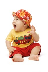 Baby in bright cloths sitting his hand to his ear mouth open looking puzzled