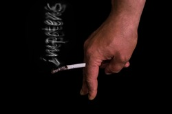 Cigarette in hand with smoke isolated on a black background. symbolizing impotence
