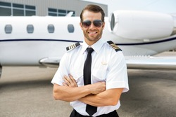 Portrait of confident pilot smiling in front of private jet
