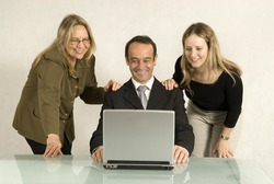 Two women standing over a man seated at a desk with their hands upon his shoulders as they all smile. Horizontally framed photo.