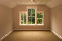 empty bedroom or study with windows looking out onto foliage