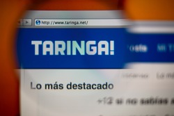 LISBON, PORTUGAL - AUGUST 27, 2014: Photo of Taringa! homepage on a monitor screen through a magnifying glass.