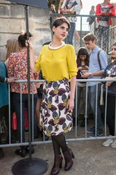 PARIS - SEPTEMBER 30, 2014: Stylish european woman with yellow shirt and skirt with flower pattern in the Tuileries Garden. Paris Fashion Week: Ready to Wear is held from September 23 to October 1.