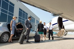 Business professional about to board private jet while airhostess and pilot greeting them