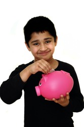 Handsome Indian kid saving money in a piggy bank