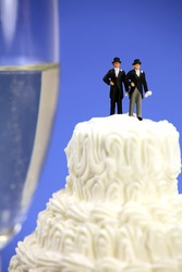 Miniature homosexual couple standing on top of a wedding cake. There is a glass of champagne in the background. Gay/same sex marriage concept.
