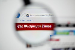 LISBON, PORTUGAL - NOVEMBER 30, 2014: Photo of The Washington Times homepage on a monitor screen through a magnifying glass.