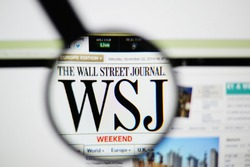 LISBON, PORTUGAL - NOVEMBER 30, 2014: Photo of The Wall Street Journal homepage on a monitor screen through a magnifying glass.