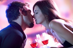 Young couple kissing in restaurant, celebrating or on romantic date