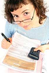 young woman doing some paperwork-filling tax form on white