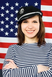 beautiful young confident sailor near the American flag