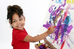 Adorable girl painting on easel over white.
