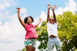 Action portrait of young African boy and girl jumping in park.