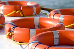 Bright orange life rings lay on top of a boat. safety, danger, rescue, security