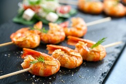 Extreme close up of appetizing grilled queen prawn tail brochettes.