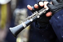 Color image of a clarinet being played on a snowy day.
