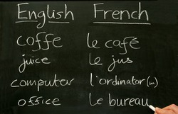 A teacher writing French lesson words on a blackboard.